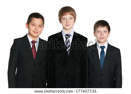 A portrait of three handsome young boys in black suits on the white background - stock photo