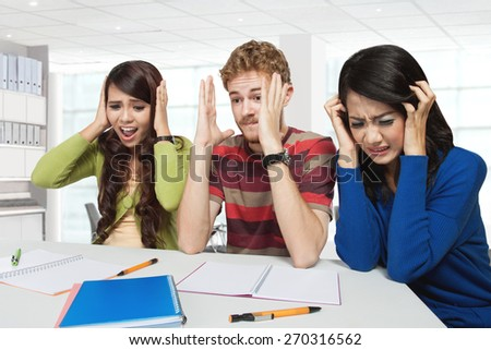 A portrait of three stress young students sitting together - stock photo