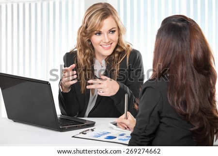 A portrait of two friendly businesswomen sitting and discussing new ideas - stock photo