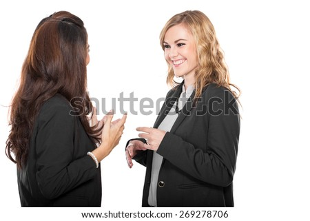 A portrait of two happy young businesswoman talking, isolated - stock photo