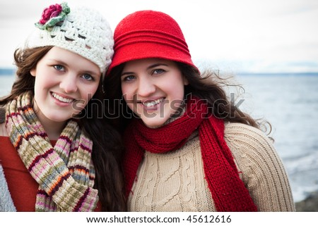 A portrait of two sisters on the beach - stock photo