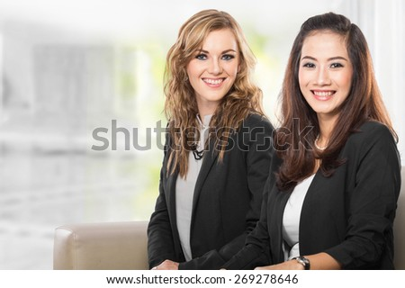 A portrait of two young businesswoman sitting next to each other, smile - stock photo