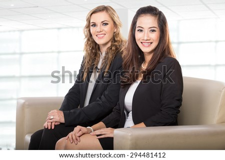 A portrait of two young businesswoman sitting next to each other, smile to the camera - stock photo