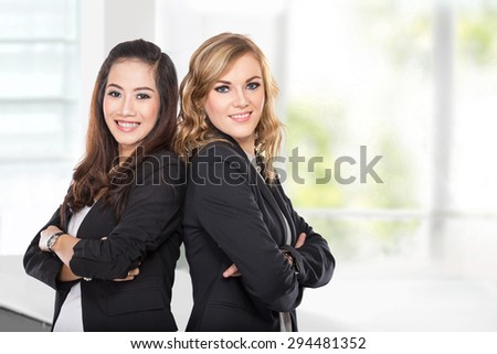 A portrait of two young businesswoman smiling while leaning against each other in the office - stock photo