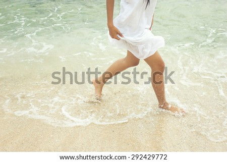A portrait of woman's foot running on the sandy beach - Selective focus - stock photo