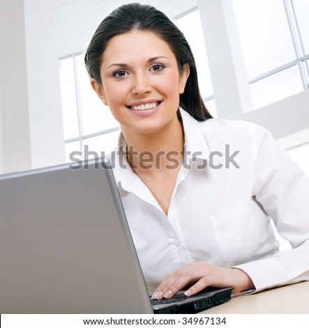 A portrait of  young businesswoman operating a lap-lop - stock photo