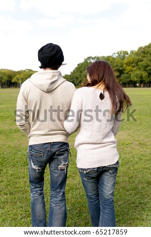 a portrait of young couple walking in the park - stock photo