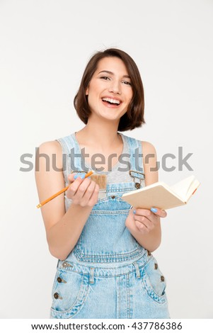 A portrait of young laughing beautiful girl, in gray shirt and denim overall, holding notebook, looking at camera, isolated on white background - stock photo