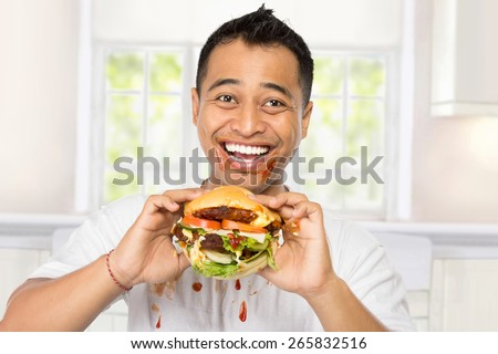 A portrait of young man eating a big burger deliciously - stock photo