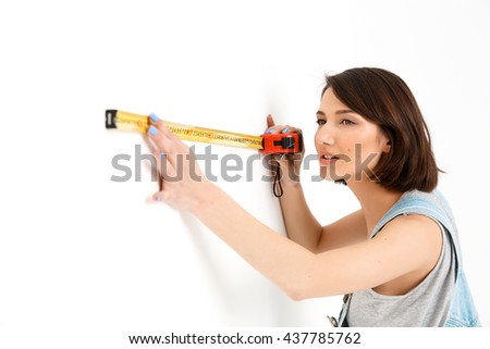 A portrait of young pretty girl, in gray shirt and denim overall, measuring the wall with tape, isolated on white background - stock photo