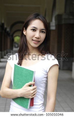 A portrait of young student holding book at campus - stock photo