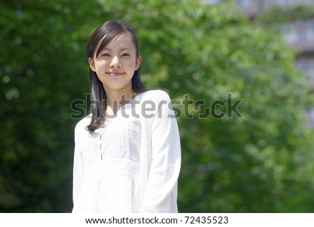 a portrait of young woman in the forest - stock photo