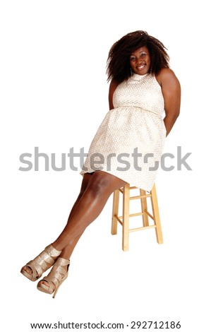 A portrait picture of a big African American woman in a beige dress relaxing in a chair, isolated for white background. - stock photo