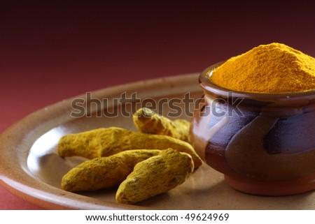 A pot full of turmeric Powder with fresh Turmeric Roots - stock photo