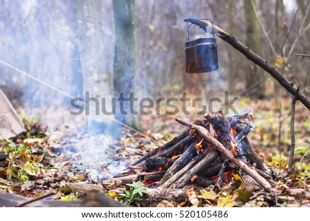 A pot of boiling water heated on the fire in the camp
