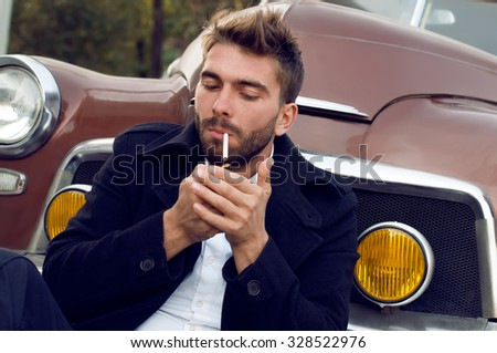 A potrait modern man is near  the car. A young  man is posing with a cigarette  near the vintage car. He is wearing a fall jacket and a white shirt. He has got a fashionable hair cut and a short beard - stock photo