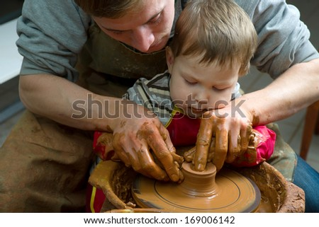 A potters hands guiding pupil hands to help him to work with the ceramic wheel - stock photo