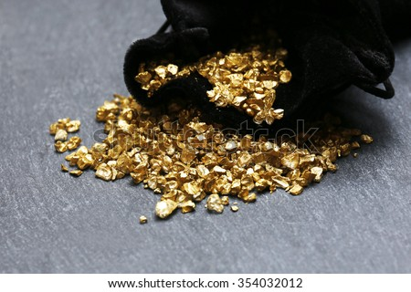 A pouch with scattered gold nugget grains, on cement background - stock photo
