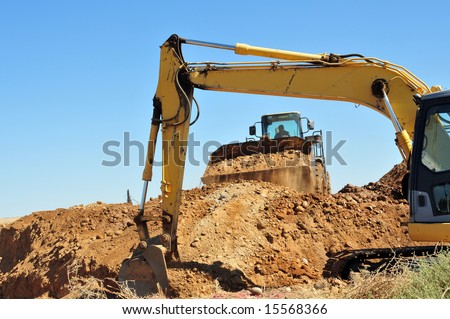 A power shovel and bucket loader team up to prepare a construction site - stock photo