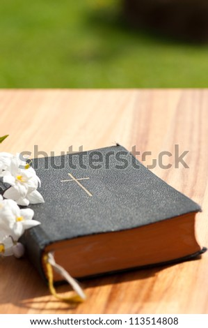 A prayerbook with jasmine on a wooden table