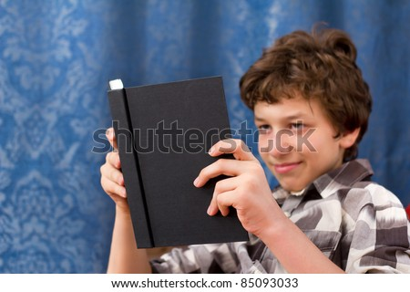 A pre-teen boy reading a black book. The boy is out of focus in the background and the book is in focus in the foreground. - stock photo