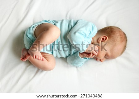 A precious newborn baby is laying on a comfortable white bed, sleeping peacefully. - stock photo