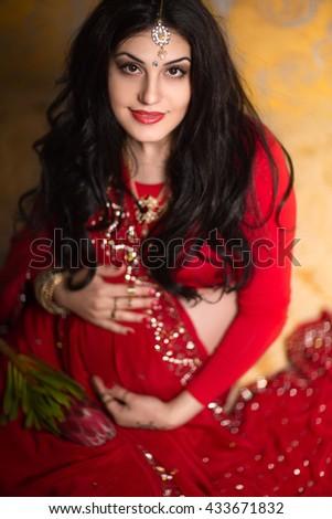 A pregnant Indian woman in a red saree. Mehendi. Saree. India. - stock photo