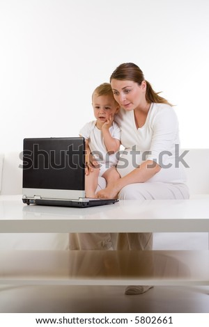 A pregnant mother and her young baby boy using on a laptop. Baby is very engrossed in the laptop. Mommy is teaching baby. Starting young, family entertaining together. - stock photo