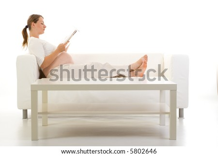 A pregnant woman lays down on the couch, relaxing as she reads. A coffee table is in the foreground. - stock photo
