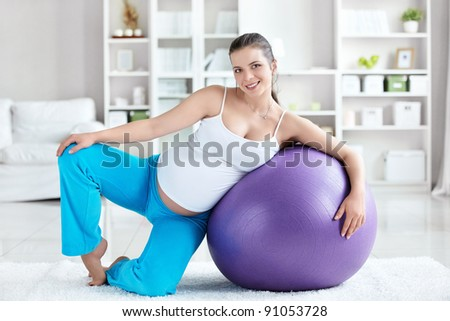 A pregnant woman with a ball at home - stock photo