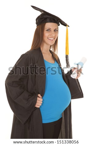 A pregnant woman with a graduation gown on. - stock photo