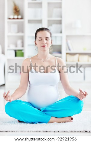 A pregnant young woman in lotus position - stock photo