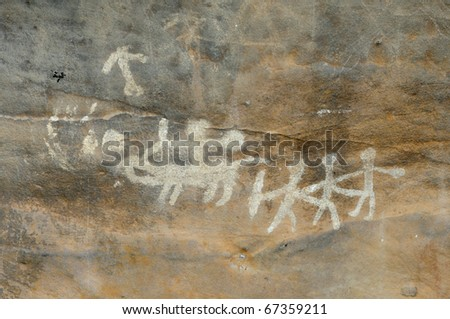 A prehistoric cave painting in Bhimbetka -India , a world heritage site which shows communal dancing. - stock photo