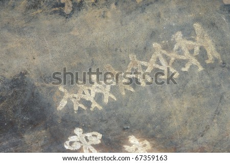 A prehistoric cave painting in Bhimbetka -India , a world heritage site which shows dancing men. - stock photo