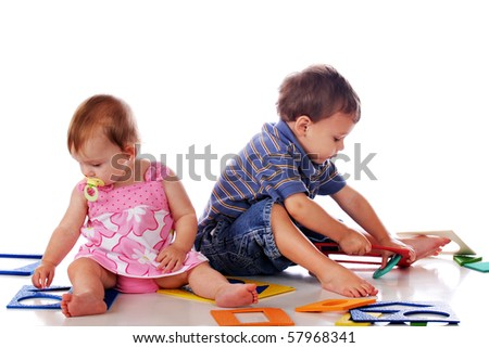 A preschool boy and baby girl attempting to assemble several small, multi-shaped puzzles.  Isolated on white. - stock photo