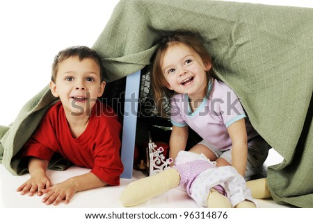 A preschool brother and sister peeking out from their play under a blanket-covered table. - stock photo
