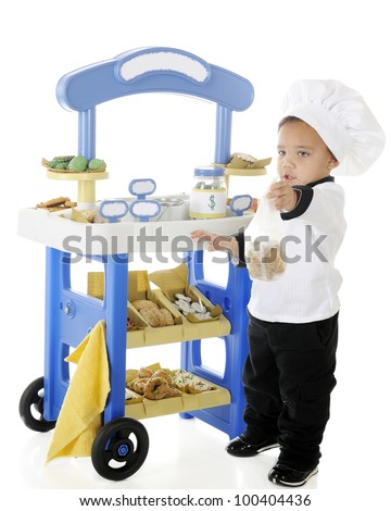 """A preschool """"chef"""" handing a bag of cookies to a customer (unseen) in front of his bakery vending stand.  The stand's signs are left blank for your text.  On a white background. - stock photo"""