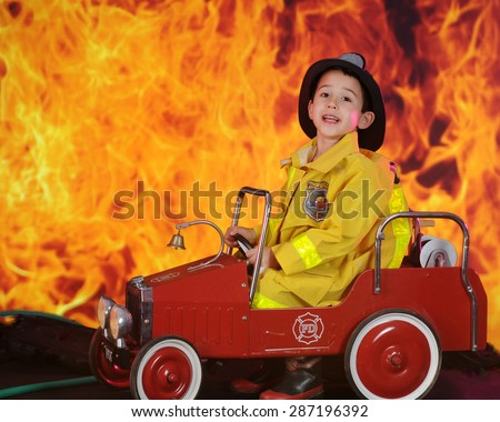 "A preschool ""fireman"" calling for reinforcements for the huge blaze behind his vintage toy fire truck. - stock photo"