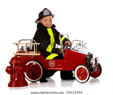 A preschooler in fireman's garb driving his truck by a fire hydrant.  Isolated on white. - stock photo