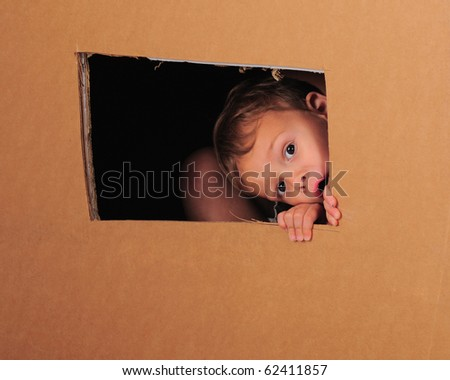 """A preschooler playing inside a large cardboard box with his brother.  He's peeking through a rough-cut """"window"""". - stock photo"""