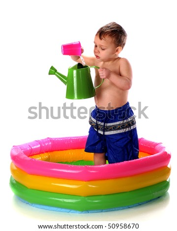 A preschooler pouring water from a plastic cup to a watering can while standing in a colorful kiddie pool.  Isolated on white. - stock photo