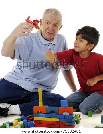 A preschooler reacting to his Grandpa as he brings a toy airplane in for a landing.  Motion blur on boy's hand. On a white background. - stock photo
