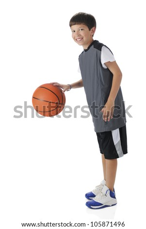 A preteen athlete dribbling his basketball.  Motion blur on ball.  On a white background.