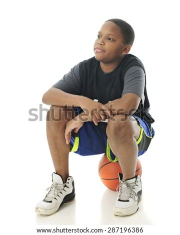 A preteen boy sitting on his basketball while looking for other players to show up.  On a white background. - stock photo