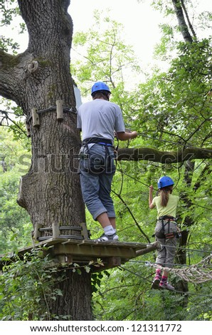 A preteen girl is walking on the tightrope. A teenage boy is standing on the platform. They are at the ropes course on the trees high up. - stock photo