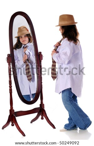 A preteen girl looking in the mirror as she tries on her grandpa's shirt, tie and dress hat.  Isolated on white.