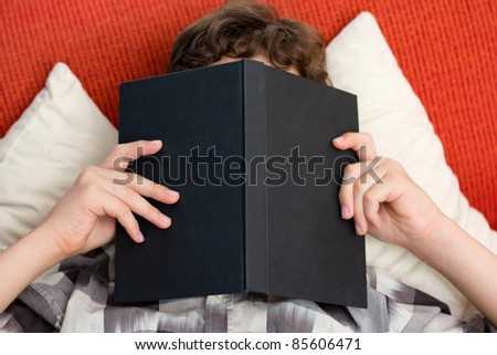 A preten boy reading his book intently as he holds it right up to his face while he lays on an orange couch with yellow pillows. - stock photo