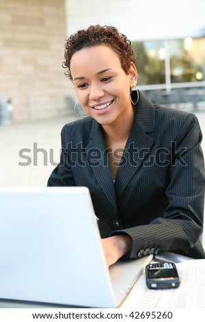 A pretty african american business woman on computer at office - stock photo