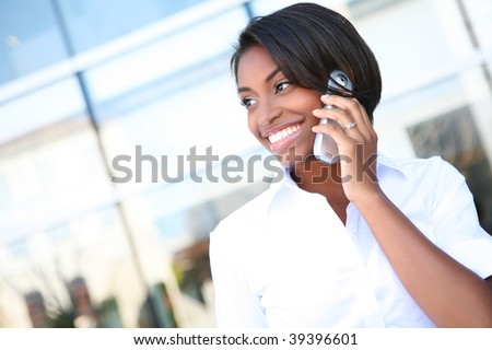 A pretty African american business woman talking on a cell phone at office building - stock photo