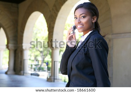 A pretty african american woman at college on phone - stock photo